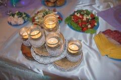 Velas ardentes em uma tabela durante um banquete imagens de stock