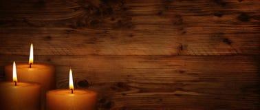 Velas ardentes na frente da parede de madeira rústica Fotografia de Stock