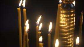 Velas ardentes na igreja no fundo preto Lit das velas Opinião do Close-up vídeos de arquivo