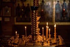 Velas ardentes na igreja na perspectiva dos ícones Imagem de Stock