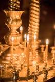 Velas ardentes na igreja na perspectiva dos ícones Imagem de Stock Royalty Free