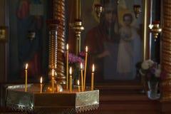 Velas ardentes no ícone da mãe do deus Fotos de Stock Royalty Free