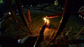 Velas ardentes no templo budista na noite Mãos do ` s dos homens velas vermelhas do fogo em grandes no gopro do templo Vela verme vídeos de arquivo
