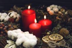 Velas ardentes vermelhas com decorações naturais Imagem de Stock
