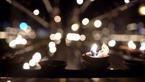 Velas ardiendo del aceite dentro del interior oscuro del templo budista almacen de video