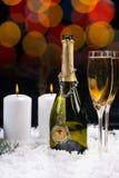Velas ardientes cerca de una botella abierta de champán Fotos de archivo libres de regalías