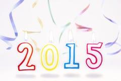 Velas ardientes con el número 2015 y flámulas que vuelan en b blanco Fotos de archivo
