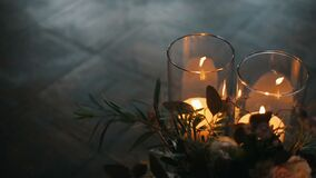 Velas ardientes con el ramo hermoso de diversas flores en un piso de entarimado Velas de quemadura en vidrios metrajes