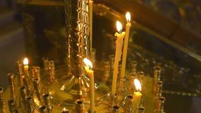 Velas ardientes de la cera antes del altar en la iglesia Foco selectivo almacen de metraje de vídeo