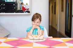 Velas ardientes de observación felices del niño en la torta de cumpleaños Imágenes de archivo libres de regalías