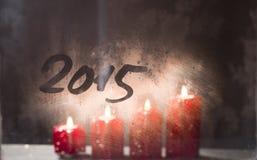 Velas ardientes del advenimiento en la ventana helada con el nuevo year 2015 Foto de archivo