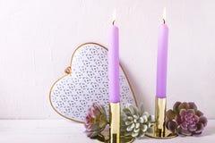 Velas ardientes del color violeta, corazón decorativo y succulents e fotos de archivo