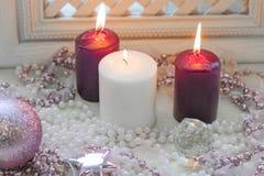 Velas ardientes del rojo y blancas con las decoraciones rosadas Imagen de archivo