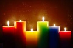 Velas ardientes en colores del arco iris Imagen de archivo libre de regalías
