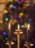 Velas ardientes en fondo de las luces de la Navidad que empaña Imagen de archivo libre de regalías