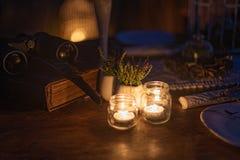 Velas ardientes en la tabla cerca de la decoración en la noche Imagen de archivo libre de regalías