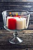 Velas ardientes en un florero de cristal en un fondo de madera Imagen de archivo libre de regalías