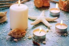 Velas ardientes en un fondo de los objetos del mar, teñido Imagen de archivo libre de regalías