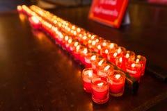Velas ardientes en un templo budista, iluminación de velas de rogación Imagen de archivo