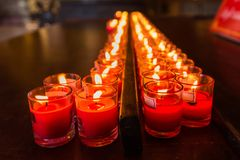 Velas ardientes en un templo budista, iluminación de velas de rogación Foto de archivo