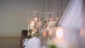 Velas ardientes gruesas que se colocan en los floreros transparentes rodeados por las materias textiles almacen de metraje de vídeo