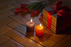 Velas ardientes, presente abierto de la caja de regalo, tulipanes rojos en el CCB de madera Imagen de archivo libre de regalías