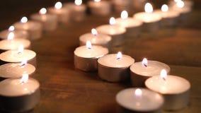 Velas ardientes Profundidad del campo baja Muchas velas de la Navidad que queman en la noche El extracto mira al trasluz el fondo almacen de video