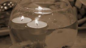 Velas ardientes que flotan en un florero decorativo retro metrajes