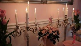 Velas ardientes, ramos de flores en la tabla en pasillo del banquete almacen de metraje de vídeo