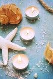 Velas ardientes y artículos marinos en un fondo de la turquesa, tinte Fotos de archivo libres de regalías