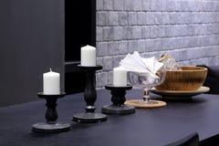 Velas blancas con la palmatoria en la tabla de madera negra en r de vida fotografía de archivo
