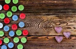 Velas coloridas de Tealight no fundo de madeira Foto de Stock
