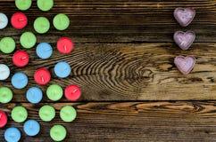 Velas coloridas de Tealight no fundo de madeira Imagem de Stock