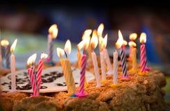 Velas coloridas en la torta de cumpleaños Imágenes de archivo libres de regalías