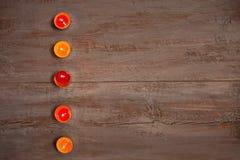 Velas coloridas en los tableros de madera fotos de archivo libres de regalías