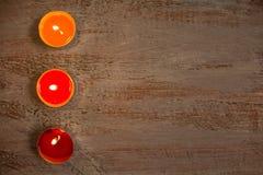Velas coloridas en los tableros de madera fotografía de archivo