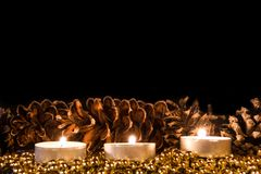 Velas con el cono del pino de la Navidad en luz atmosférica Foto de archivo libre de regalías