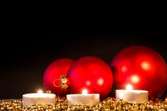 Velas con las bolas rojas de la Navidad en luz atmosférica Imagen de archivo libre de regalías