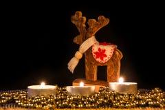 Velas con los ciervos de madera de la Navidad en luz atmosférica Foto de archivo libre de regalías