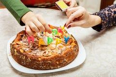 Velas da iluminação em um bolo de aniversário Fotografia de Stock Royalty Free