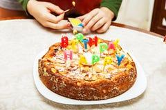 Velas da iluminação em um bolo de aniversário Fotos de Stock Royalty Free