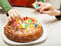 Velas da iluminação em um bolo de aniversário Imagens de Stock Royalty Free