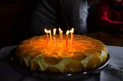Velas da iluminação em um bolo de aniversário Imagens de Stock