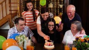 Velas da iluminação da mãe em seu bolo de aniversário da filha no partido filme