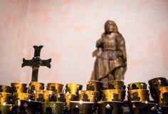Velas da oração na igreja Católica com crucifixo e simbolismo imagens de stock
