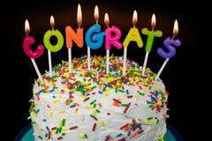 Velas de Congrats en la torta acodada fotos de archivo