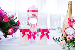 Velas de la boda con las cintas rosadas y la botella de oro Fotos de archivo libres de regalías