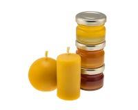 Velas de la cera de abejas y tarros de la miel Foto de archivo libre de regalías