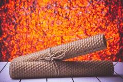 Velas de la cera de abejas en bukeh anaranjado agradable del fondo Fotografía de archivo
