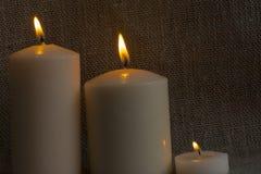 3 velas de la cera, fuego, quemando Imagen de archivo libre de regalías